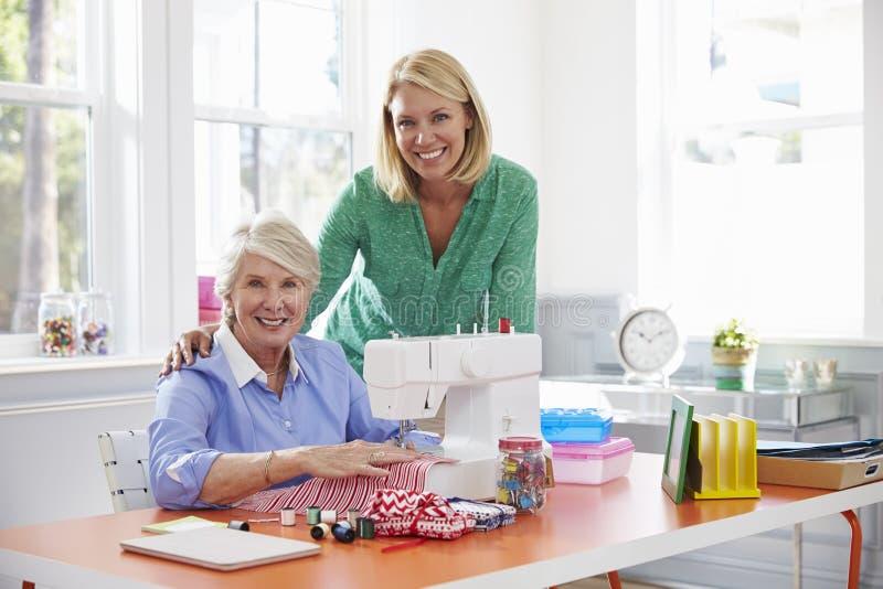 Máquina de costura superior do uso da filha da mãe e do adulto em casa foto de stock