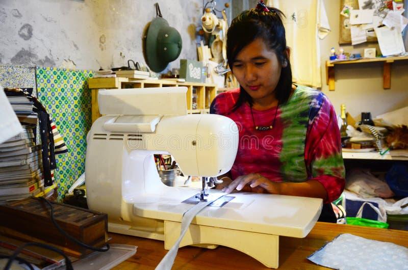 Máquina de costura tailandesa da mulher na noite imagem de stock royalty free