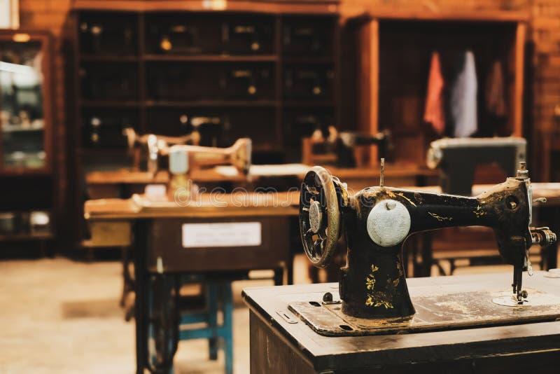 Máquina de costura velha no local de trabalho da fábrica do vestuário imagens de stock royalty free