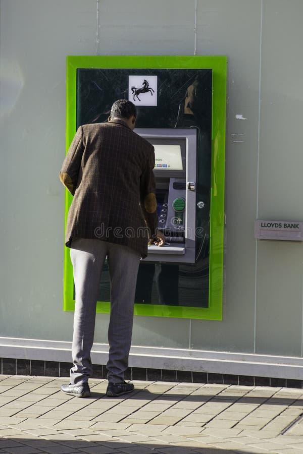 Máquina de dinheiro do Lloyds Bank que está sendo usada pelo homem asiático foto de stock