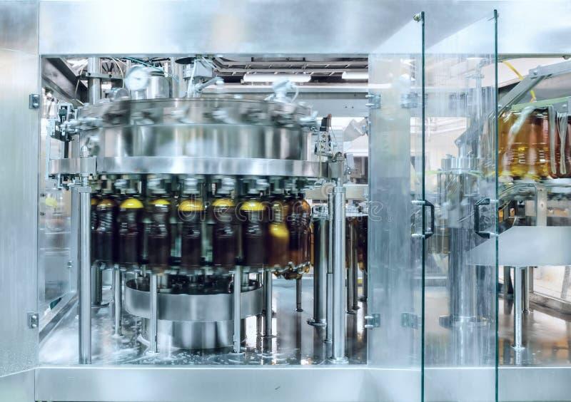 A máquina de enchimento derrama a cerveja em garrafas plásticas do ANIMAL DE ESTIMAÇÃO foto de stock royalty free