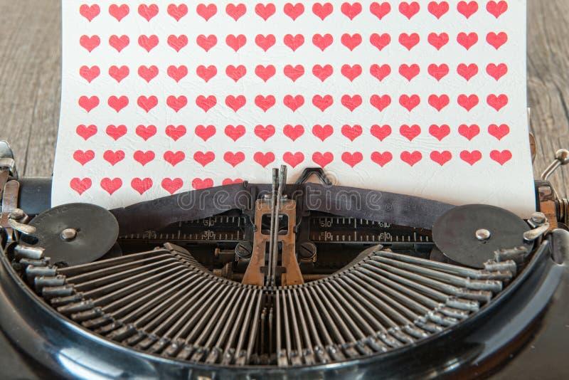 máquina de escrever com corações vermelhos no papel imagem de stock