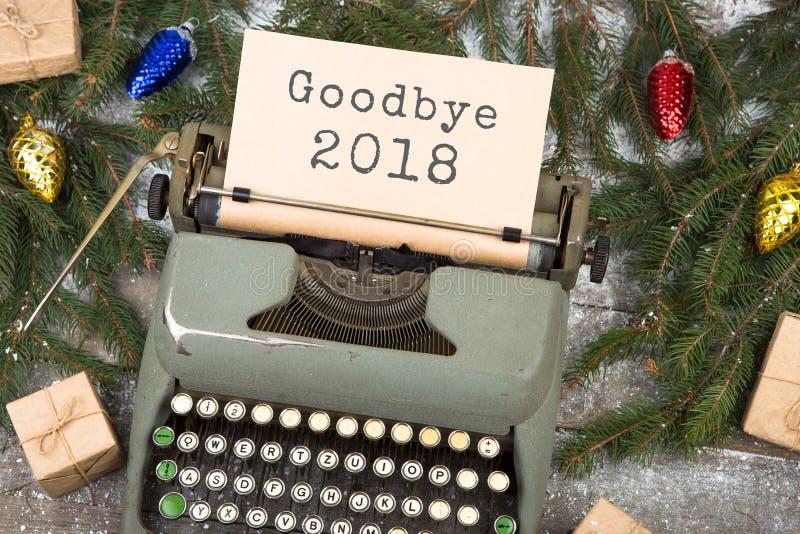 Máquina de escrever com texto 'adeus 2018 ', ramos do abeto vermelho e caixas de presente em uma tabela de madeira fotos de stock royalty free