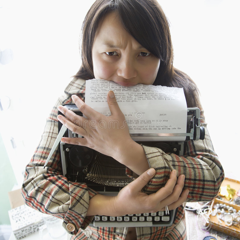 Máquina de escrever da terra arrendada da mulher. imagem de stock