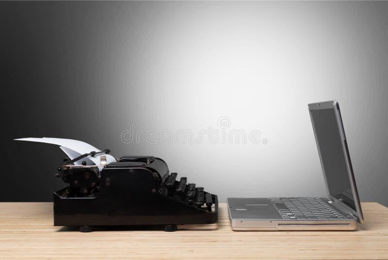 Máquina de escrever e portátil velhos na tabela de madeira fotos de stock royalty free