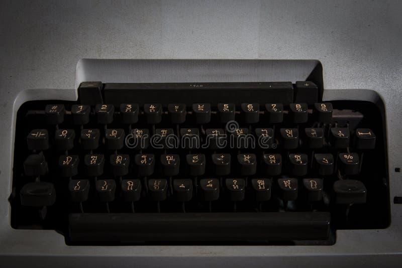 Máquina de escrever tailandesa na sala escura foto de stock