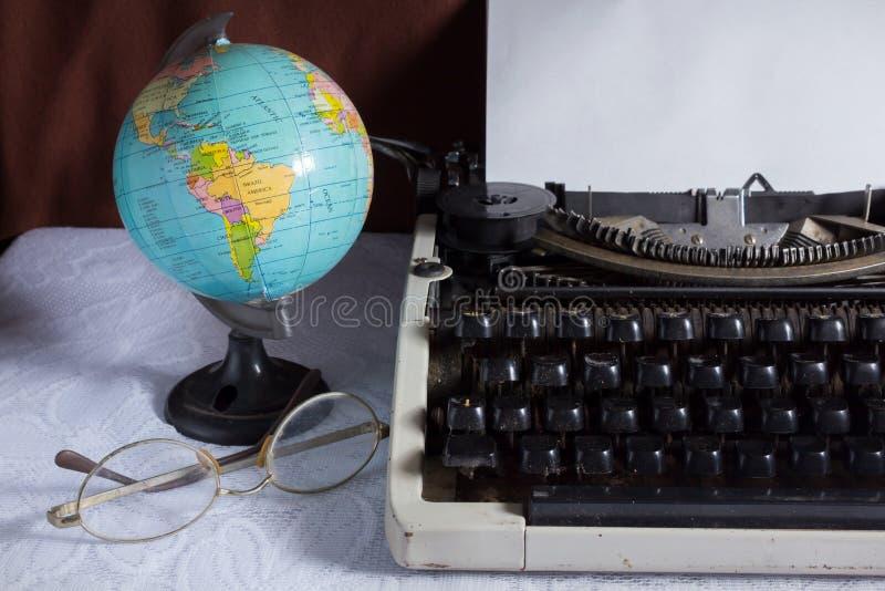 Máquina de escrever velha com globo e monóculos. fotografia de stock royalty free