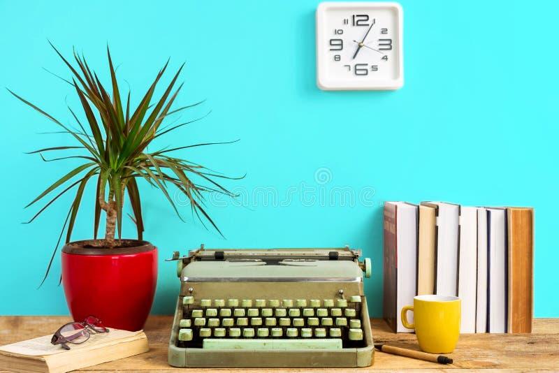 Máquina de escribir, libros y reloj de trabajo del escritorio en la pared fotografía de archivo libre de regalías