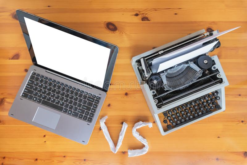 Máquina de escribir vieja contra el nuevo ordenador portátil en la tabla Concepto de progreso de la tecnología fotografía de archivo libre de regalías