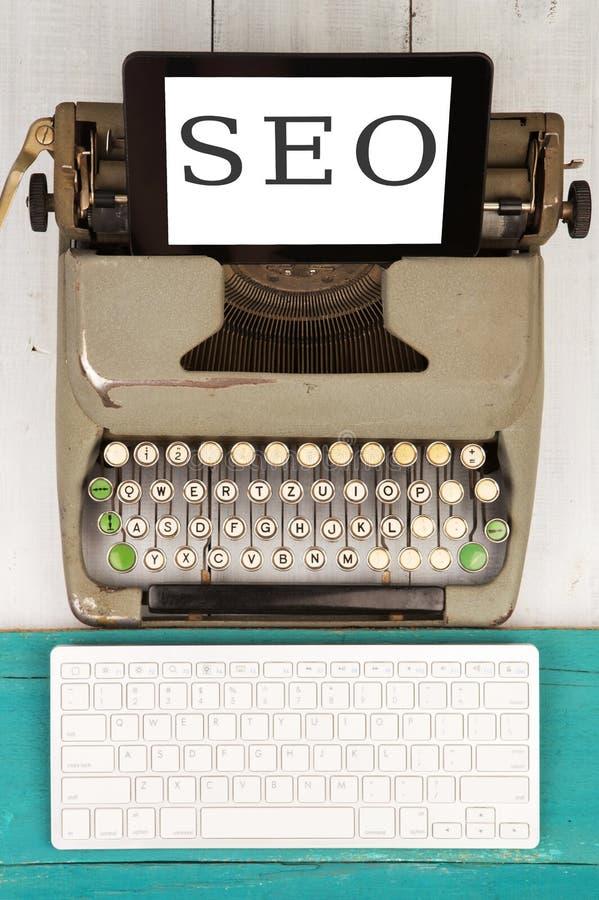 Máquina de escribir vieja, nuevo teclado de ordenador y PC de la tableta con el texto y x22; SEO& x22; fotos de archivo
