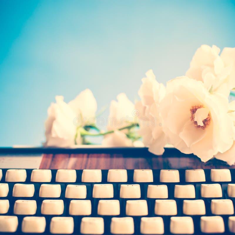 Máquina de escribir y flores fotos de archivo