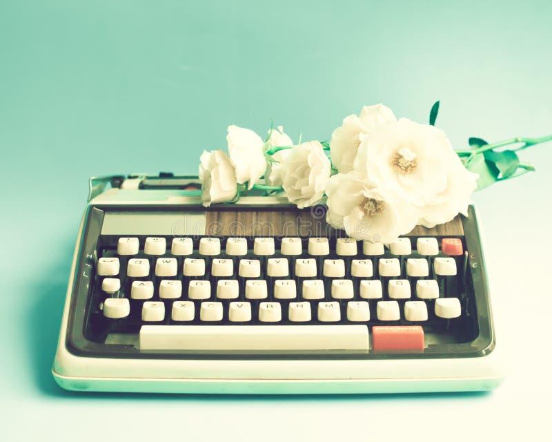 Máquina de escribir y flores fotografía de archivo