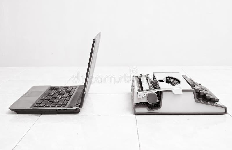 Máquina de escribir y ordenador portátil en comparar entre el equipo bajo y alto del negocio Concepto de progreso de la tecnologí imagen de archivo