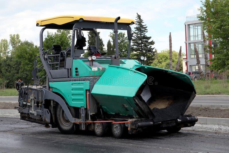 Máquina de extensión del asfalto. Pavimentación del camino imagen de archivo libre de regalías