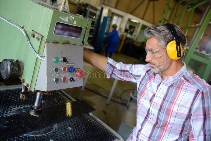 Máquina de funcionamento do trabalhador na fábrica fotos de stock