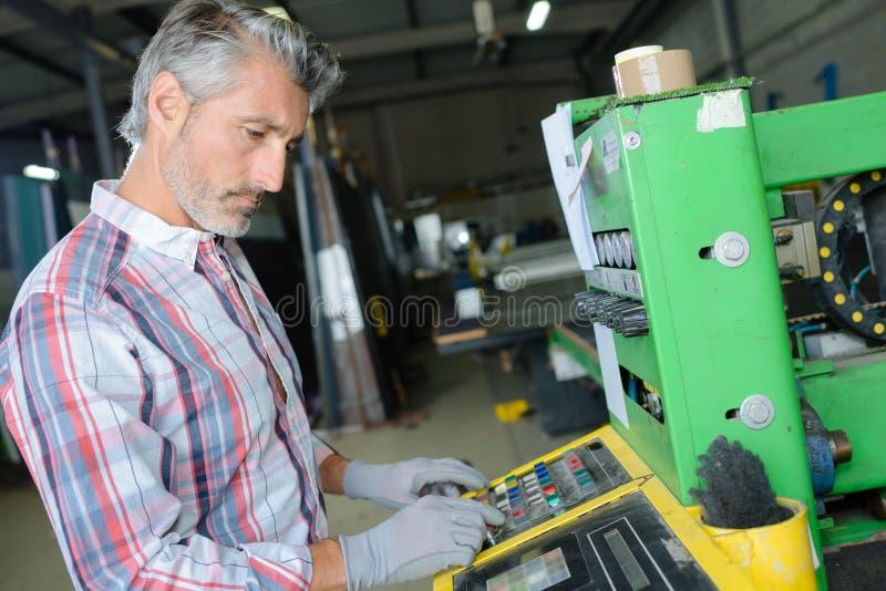 Máquina de funcionamiento del trabajador en fábrica fotografía de archivo libre de regalías