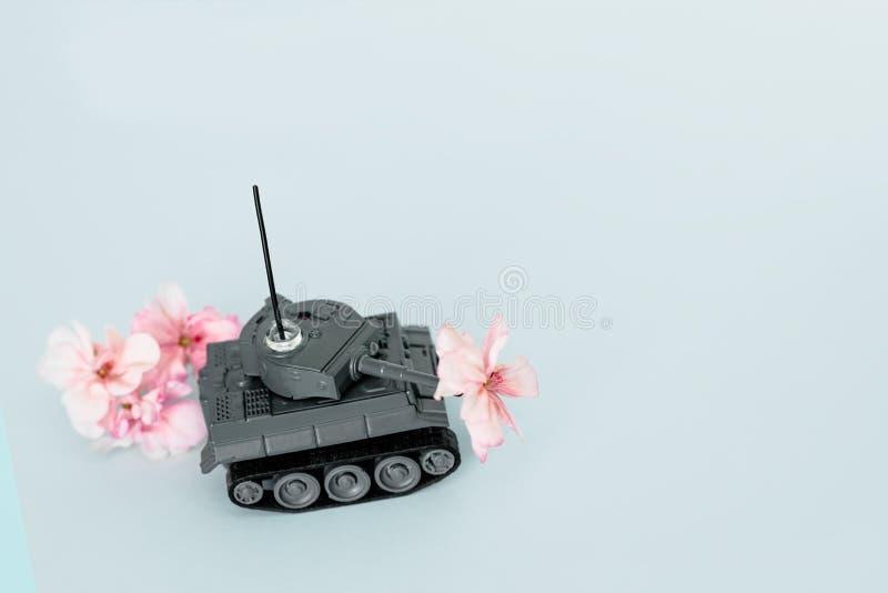 Máquina de guerra con una flor en la parte posterior, la paz y la guerra, acción militar, una flor en el barril de un tanque, esp imagen de archivo libre de regalías