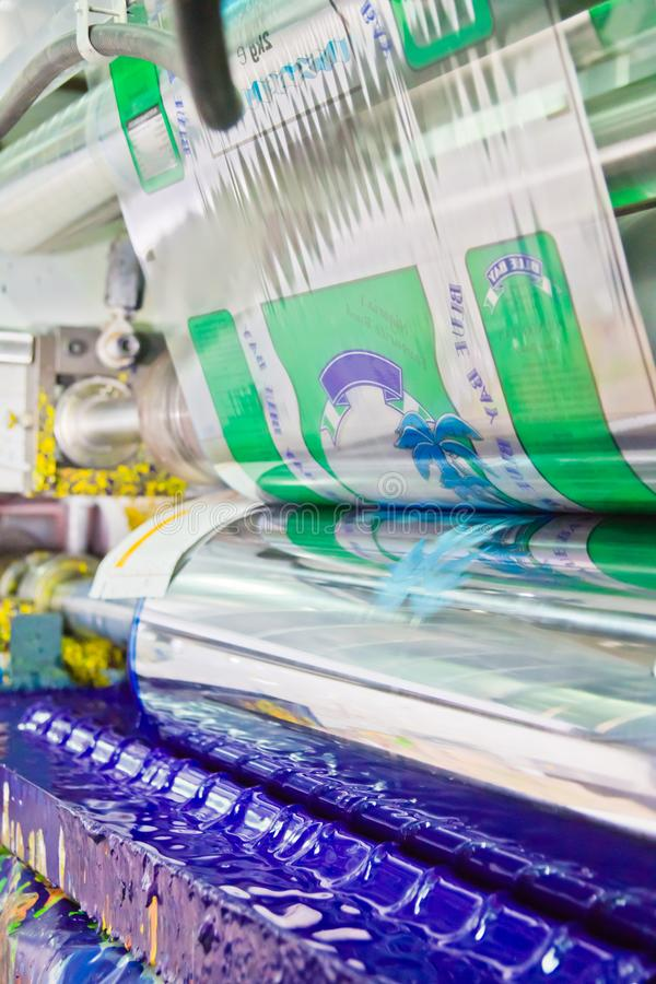 Máquina de impressão industrial da rotogravura com os rolos da tinta e de filme plástico que correm na fábrica imagens de stock royalty free