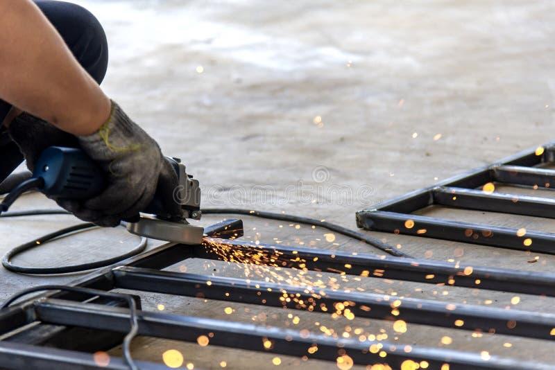 Máquina de la amoladora de la mano del uso del trabajador que muele la tubería de acero imagen de archivo libre de regalías