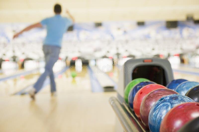 Máquina de la bola de bowling con el bowling del hombre foto de archivo libre de regalías