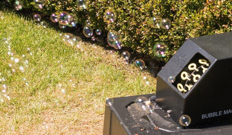 Máquina de la burbuja que sopla hacia fuera burbujas de jabón imagenes de archivo