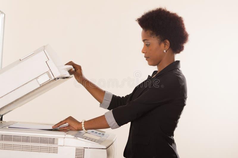 Máquina de la copia de funcionamiento de la mujer de la oficina fotografía de archivo