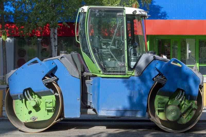 Máquina de la reparación del camino - rodillo para el balanceo del asfalto Colores azulverdes Calle de la ciudad Vista lateral foto de archivo libre de regalías