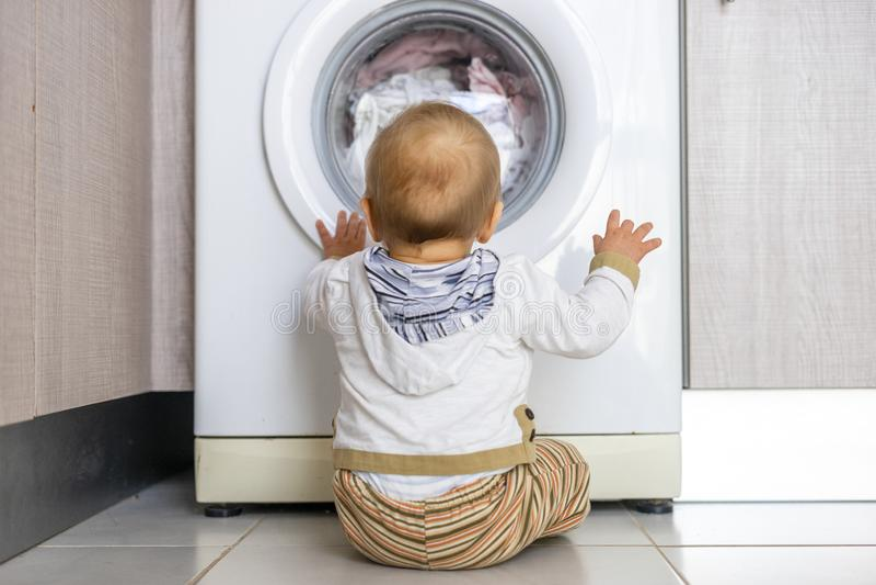 A máquina de lavar branca mantém ocupado o bebê pequeno fotografia de stock royalty free
