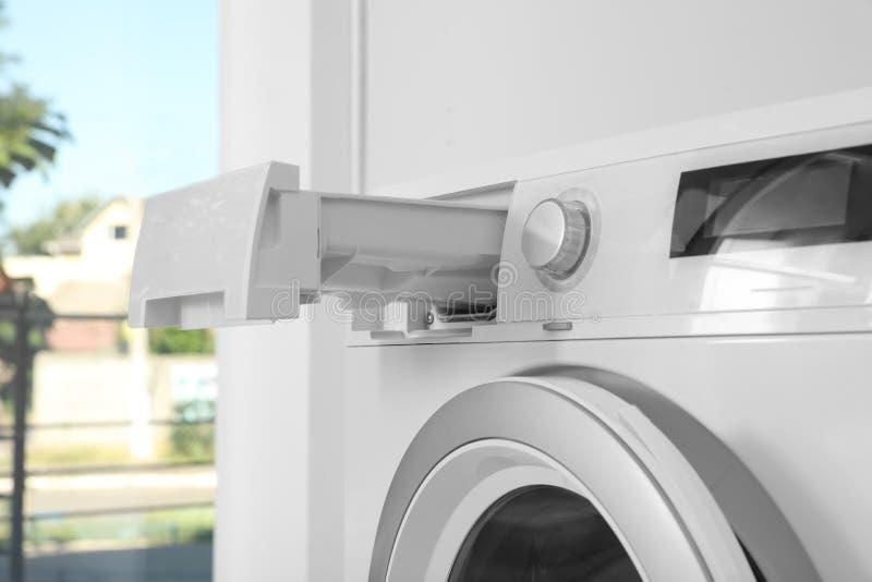 Máquina de lavar com a gaveta detergente aberta na lavandaria foto de stock royalty free