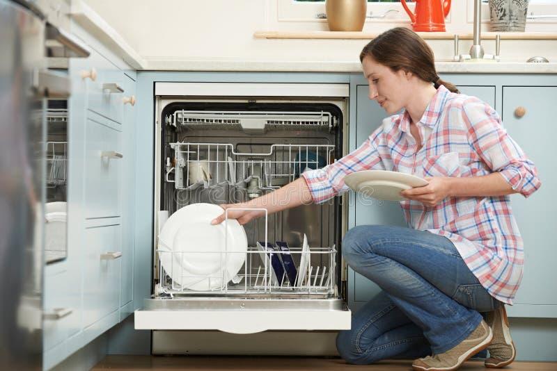 Máquina de lavar louça In Kitchen da carga da mulher fotos de stock