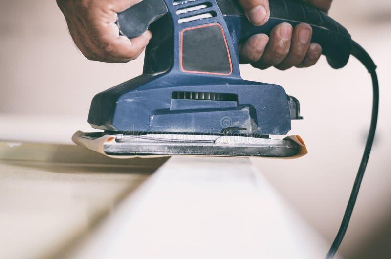 A máquina de lixar orbital no uso, porta velha de lixamento para um novo lambe da pintura fotografia de stock royalty free