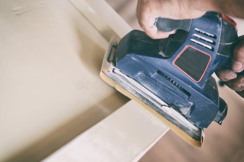 A máquina de lixar orbital no uso, porta velha de lixamento para um novo lambe da pintura fotos de stock