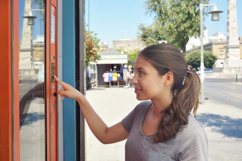 Máquina de vending chinesa Menina atrativa bebidas bronzeadas da compra no verão O estudante novo ou o turista fêmea que escolhem imagens de stock royalty free