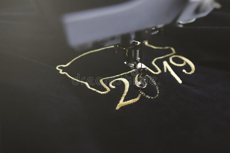 Máquina del bordado que cose motivo chino del Año Nuevo 2019 con hilado precioso del oro en el terciopelo negro en humor ligero b imagenes de archivo
