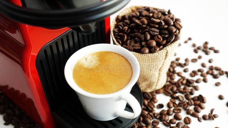 Máquina del café de Expresso con café preparado fresco y habas asadas en la taza blanca imagenes de archivo