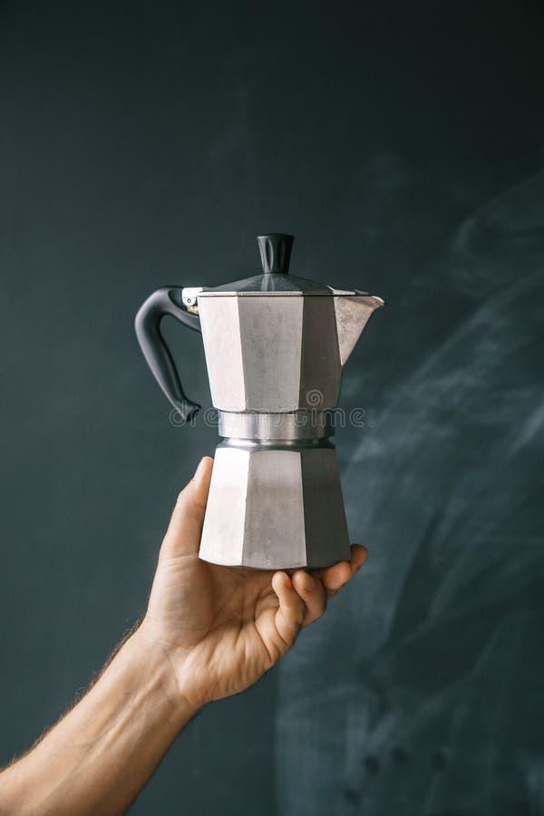 Máquina del café del géiser en las manos masculinas en un fondo negro de la pizarra imagen de archivo