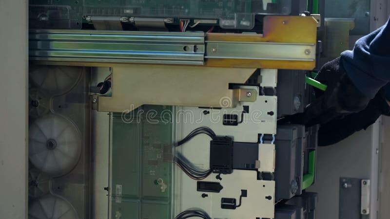 Máquina del cajero automático desde adentro, cajero automático de mantenimiento del guardia del CIT, transacción bancaria fotos de archivo