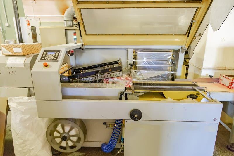 Máquina del envasado de alimentos Galletas del embalaje en las cajas de cartón y capa por la película en la cadena de producción  foto de archivo