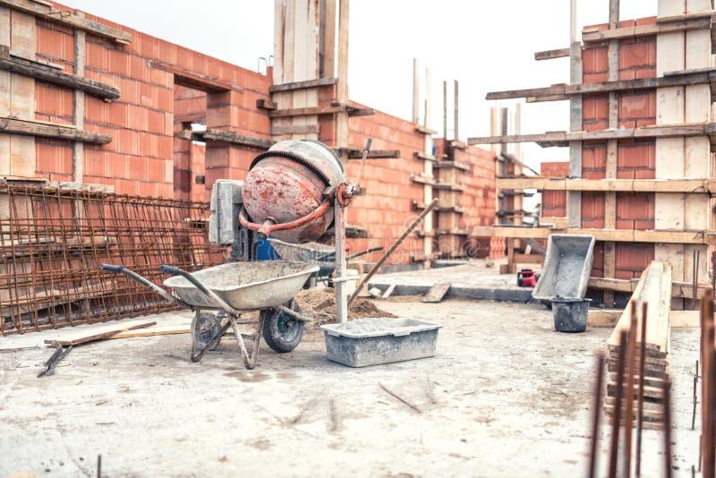 Máquina del mezclador de cemento en el emplazamiento de la obra, las herramientas, la carretilla, la arena y los ladrillos en la  imagen de archivo libre de regalías