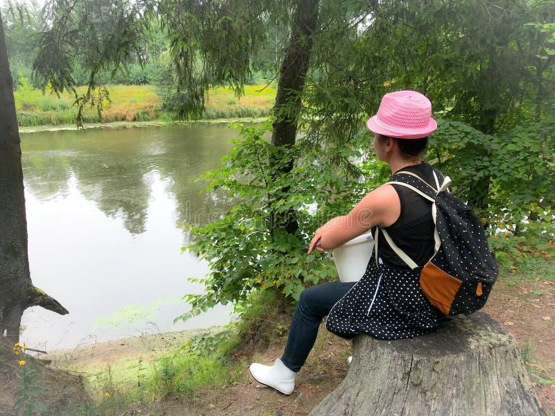 Máquina desbastadora do cogumelo da mulher com um chapéu em sua cabeça e em uma trouxa sobre seus ombros Sentou-se em um coto em  fotos de stock royalty free