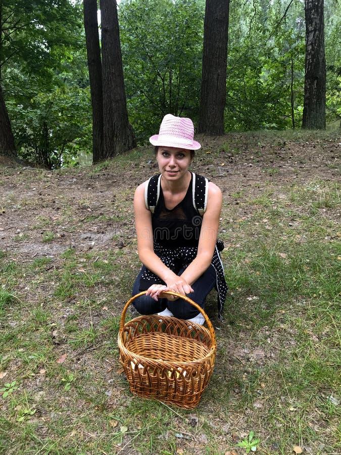 Máquina desbastadora satisfeita do cogumelo da mulher com um chapéu em sua cabeça e em uma trouxa sobre seus ombros Eu sentei-me  fotos de stock royalty free
