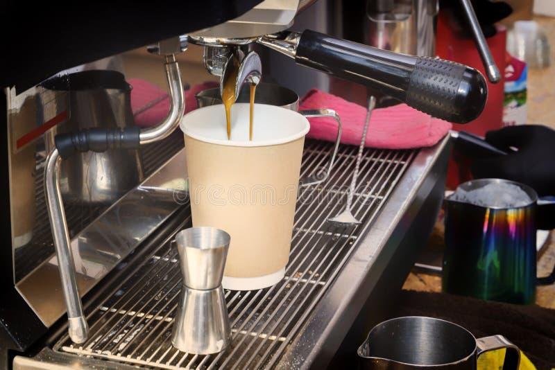 A máquina do café prepara o café fresco e derrama-o em um copo de papel no contador da barra imagem de stock royalty free