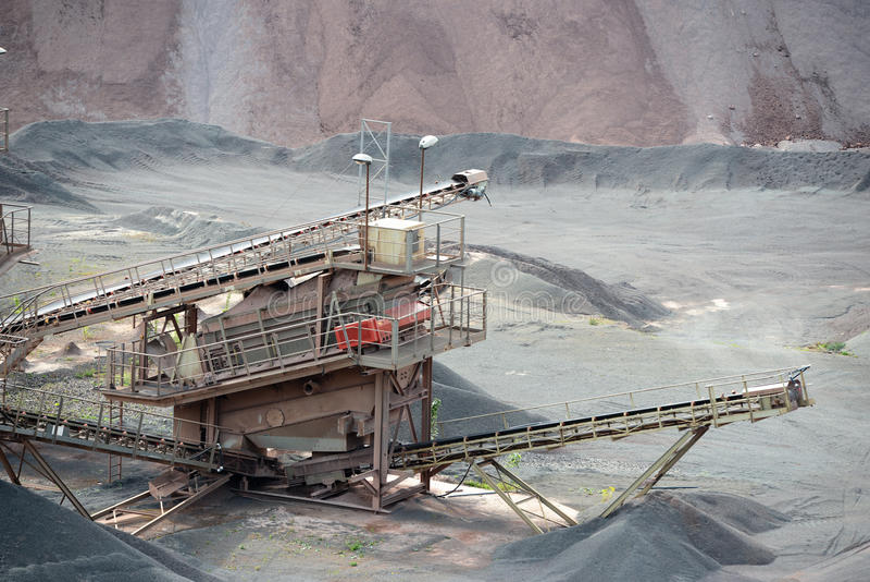 Máquina do triturador de pedra em uma mina de poço aberto imagem de stock