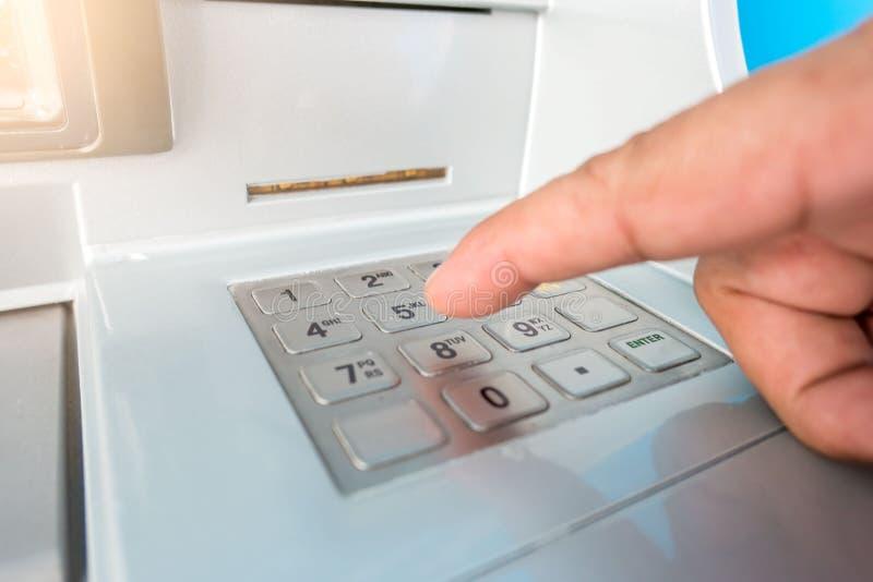 A máquina e o dedo do ATM do close up entregam entrar pressionando a senha para retirar cédulas do dinheiro fotografia de stock