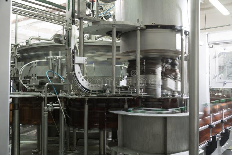 A máquina enche garrafas plásticas da cerveja na fábrica da cerveja foto de stock