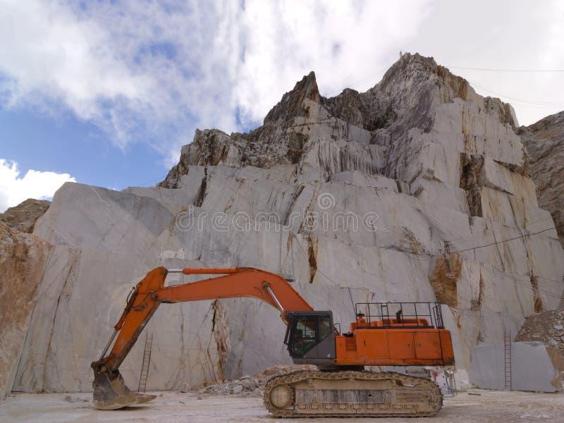Máquina escavadora alaranjada em uma pedreira de mármore branca em Carrara imagens de stock royalty free