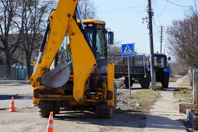 A máquina escavadora amarela com uma cubeta está na estrada asfaltada reparada imagens de stock