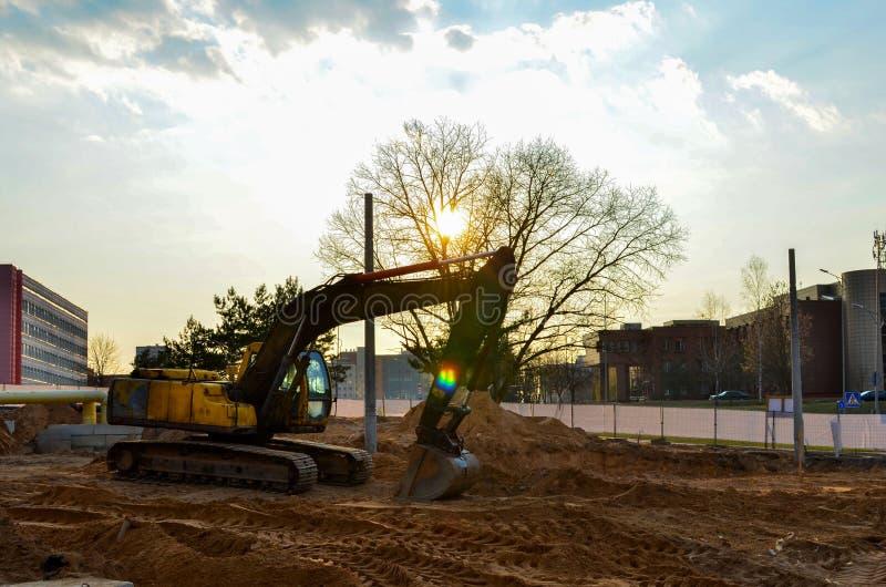 Máquina escavadora amarela em um canteiro de obras durante terraplenagens e colocação das tubulações subterrâneas e comunicações  fotografia de stock