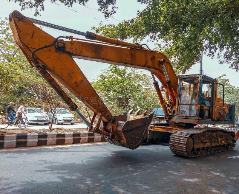 Máquina escavadora amarela em uma estrada fotos de stock royalty free