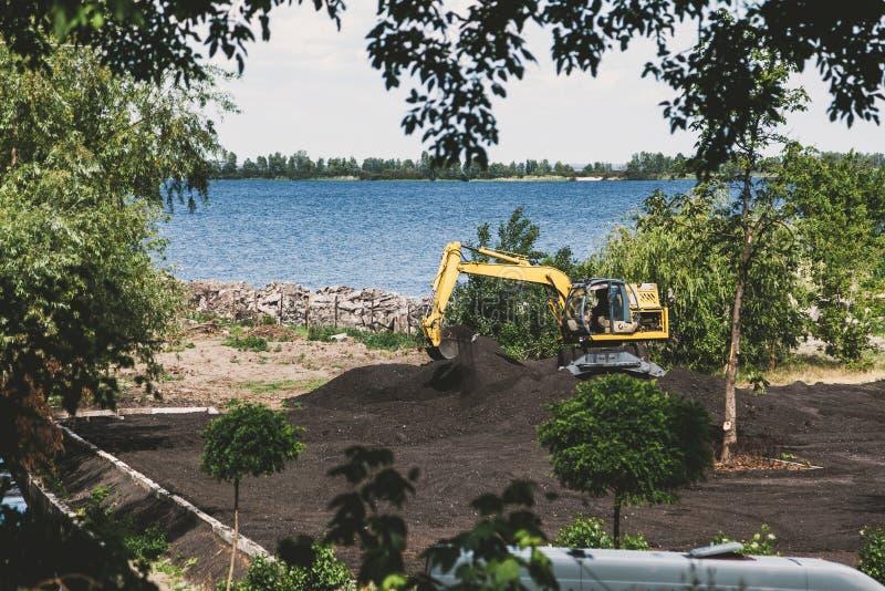 A máquina escavadora amarela escava o solo no banco de rio fotos de stock royalty free